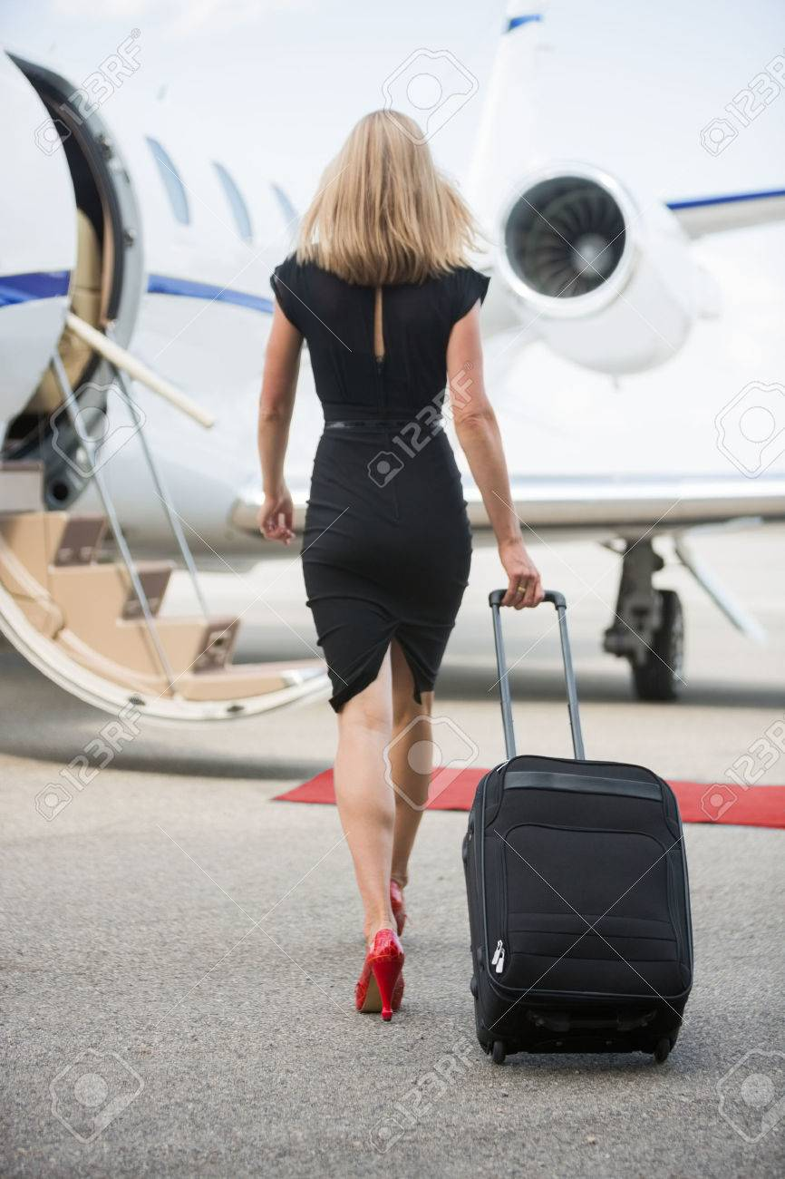 Full length rear view of wealthy woman with luggage walking towards private jet at airport terminal Stock Photo - 25291892