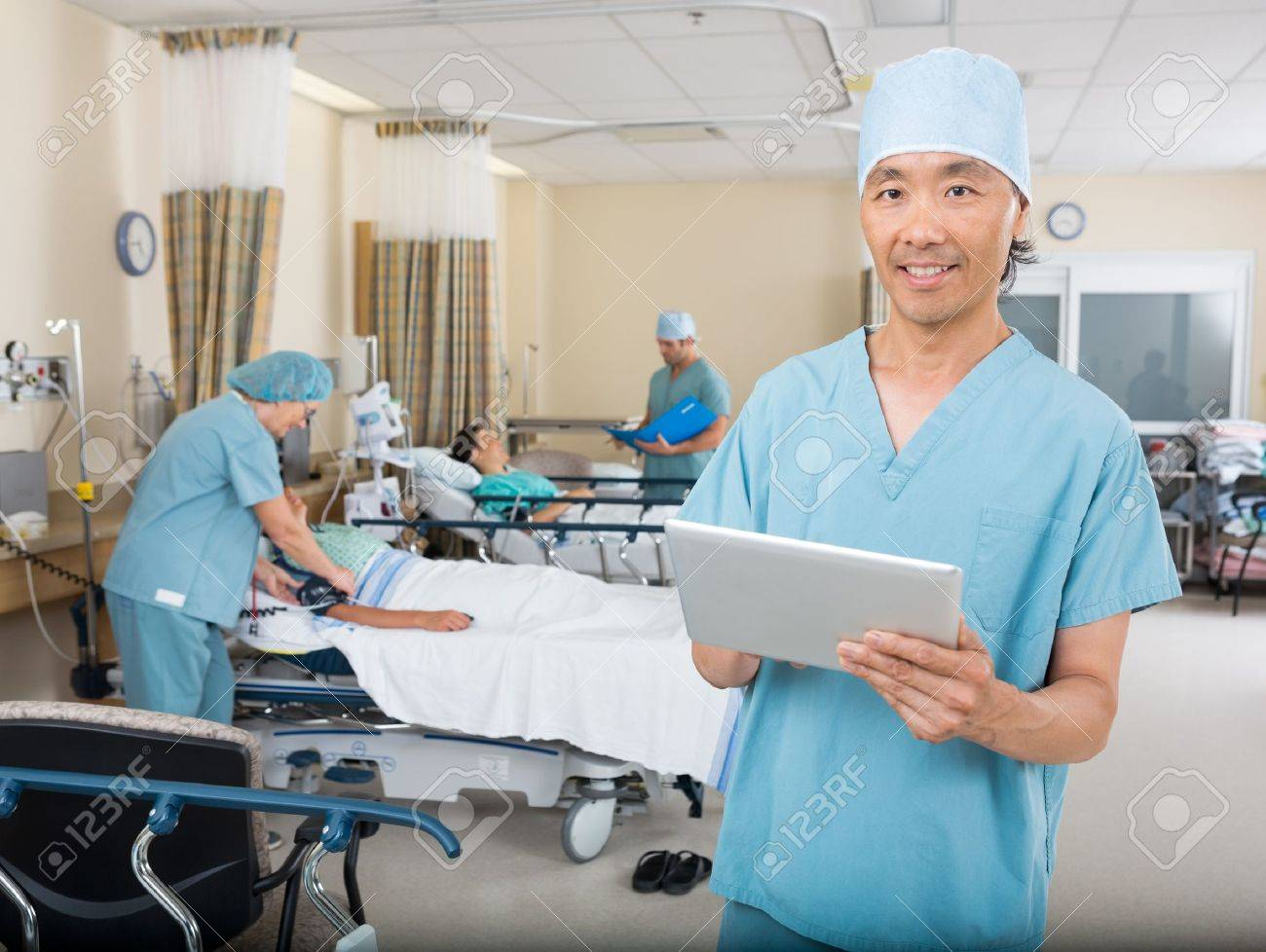 Portrait of male nurse with digital tablet standing in hospital PACU Stock Photo - 25768940
