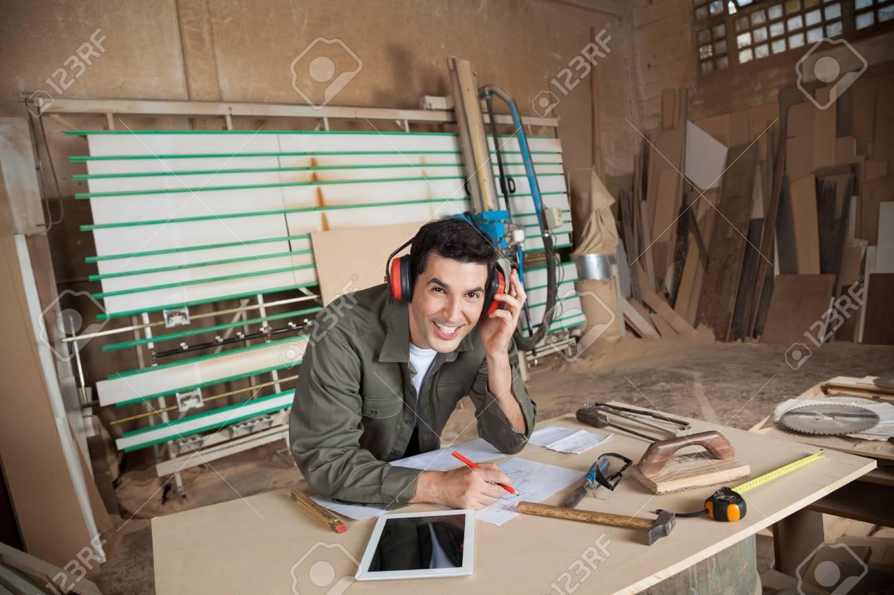 Happy carpenter working on blueprint in workshop stock photo happy carpenter working on blueprint in workshop stock photo 33557282 malvernweather Images