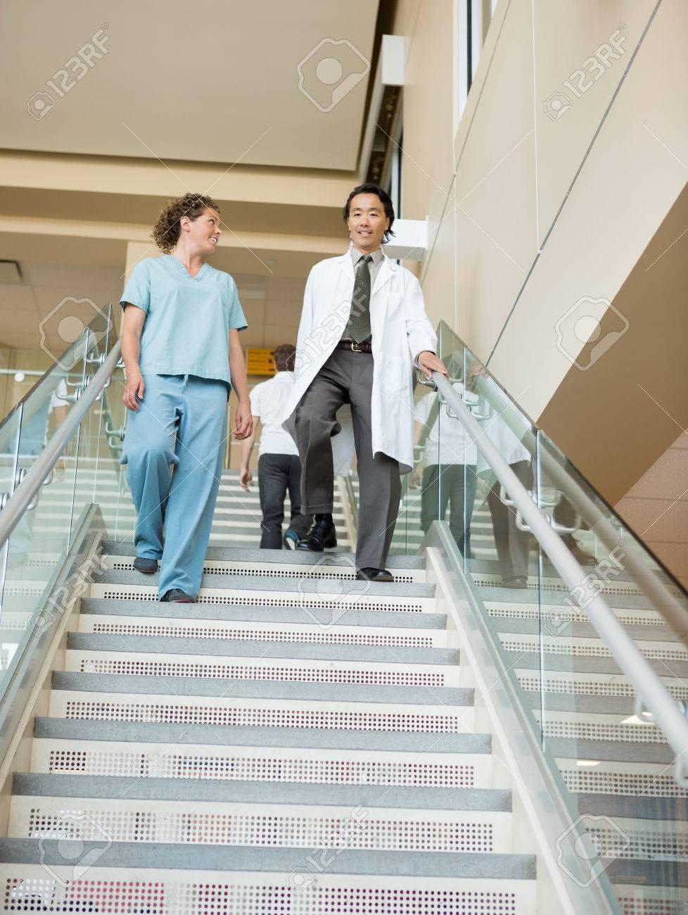 女性看護師と医師の病院で階段を...