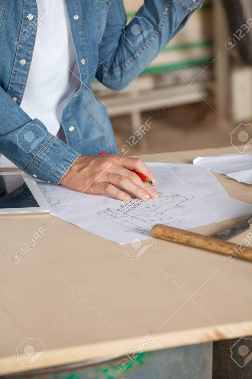 Female carpenter with blueprint at table stock photo picture and female carpenter with blueprint at table stock photo 33825043 malvernweather Images