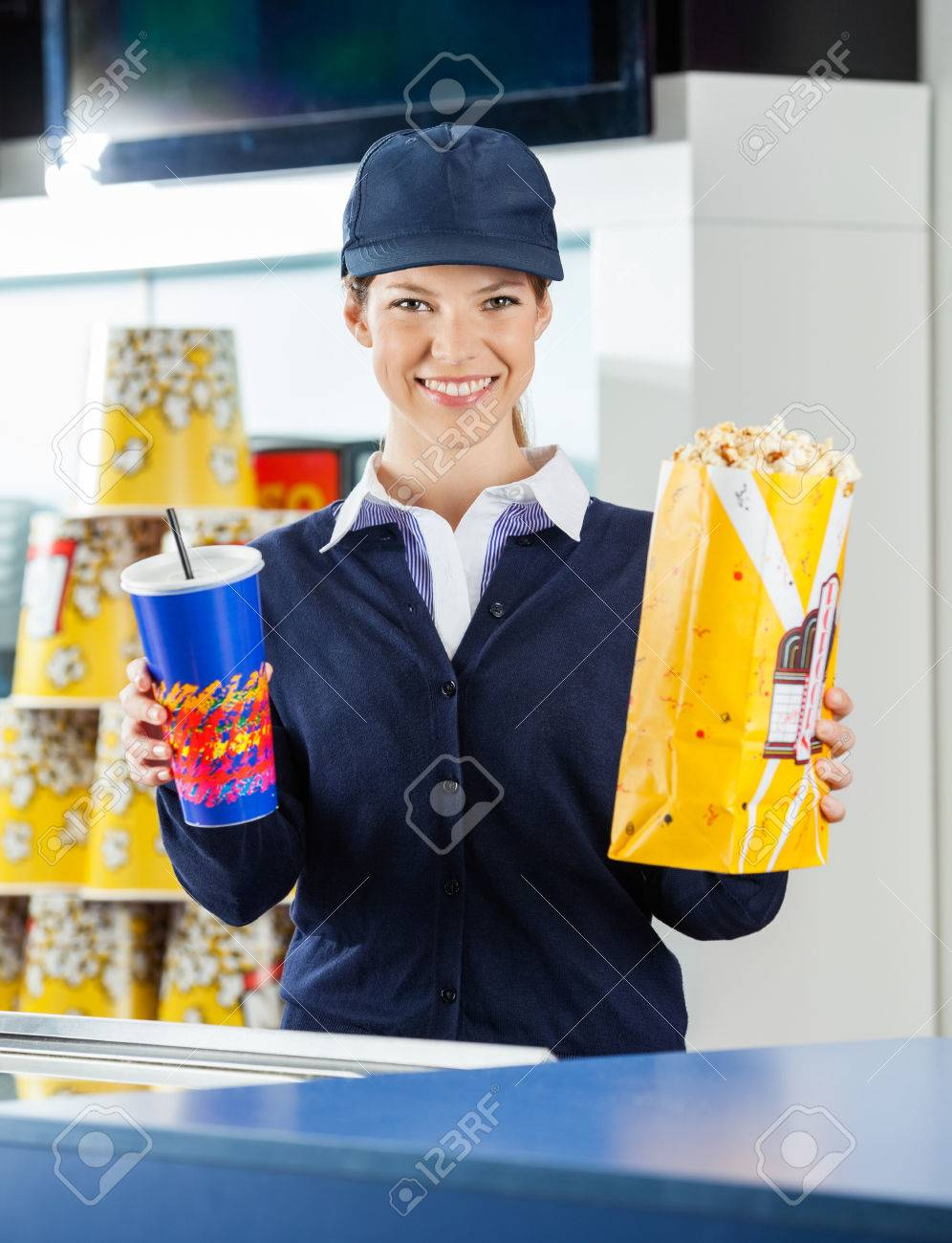 happy worker holding popcorn and drink cinema concession counter happy worker holding popcorn and drink cinema concession counter stock photo 34105354