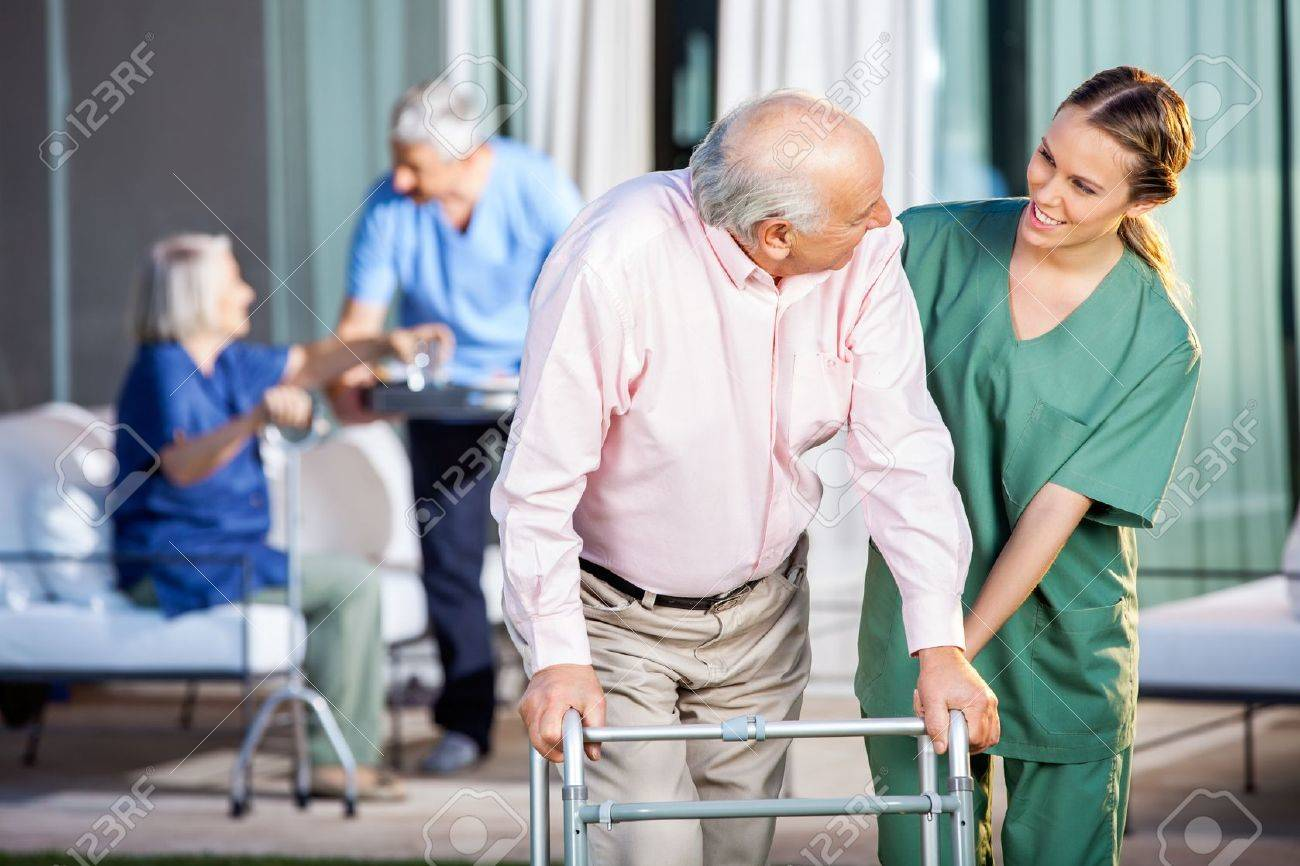 Happy Caretaker Assisting Senior Man In Using Zimmer Frame Stock Photo - 35135408