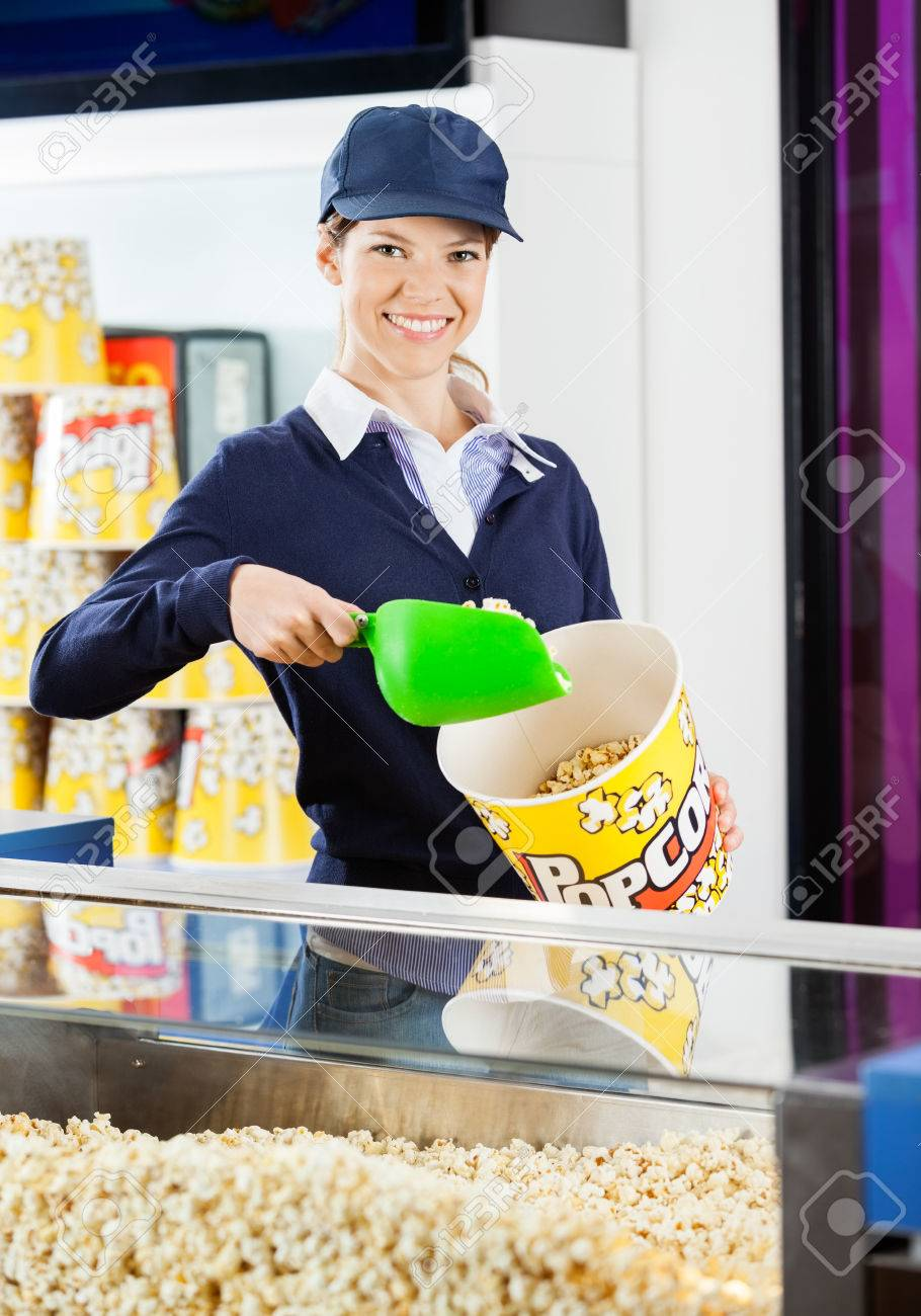 worker pouring popcorn in bucket at cinema concession stand stock stock photo worker pouring popcorn in bucket at cinema concession stand