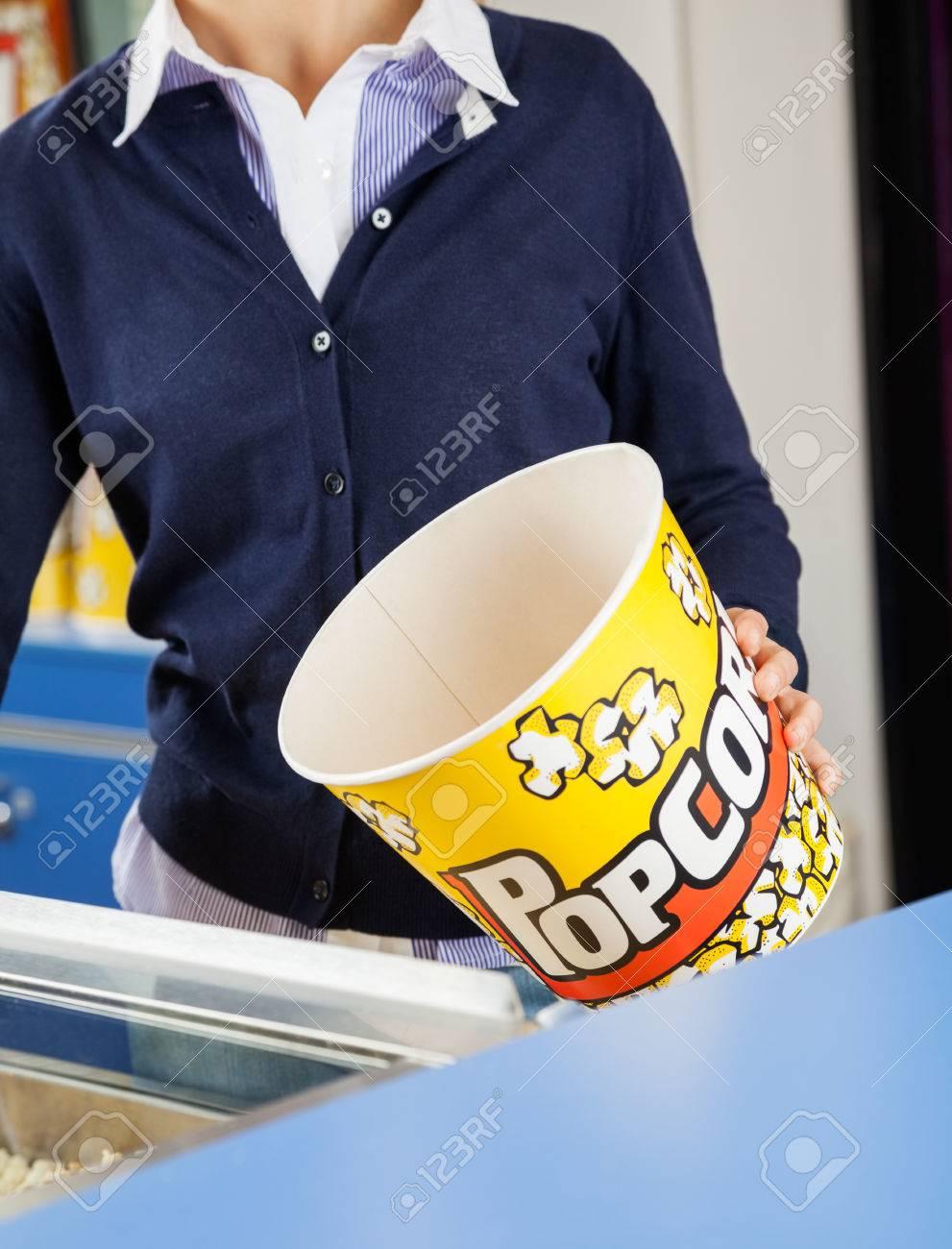 worker holding empty popcorn bucket at concession stand stock stock photo worker holding empty popcorn bucket at concession stand