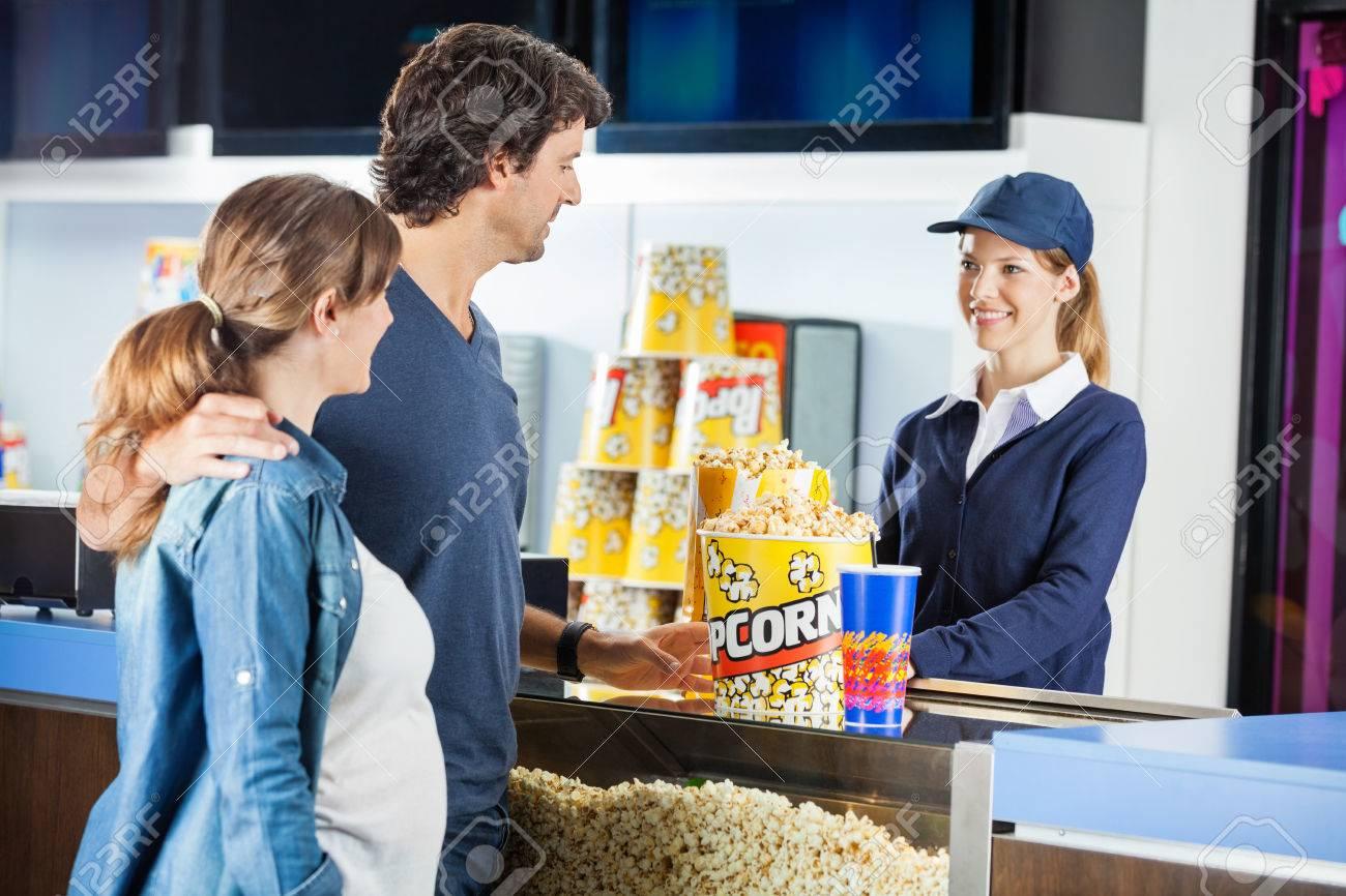 expectant couple buying popcorn at cinema concession stand stock expectant couple buying popcorn at cinema concession stand stock photo 38644062