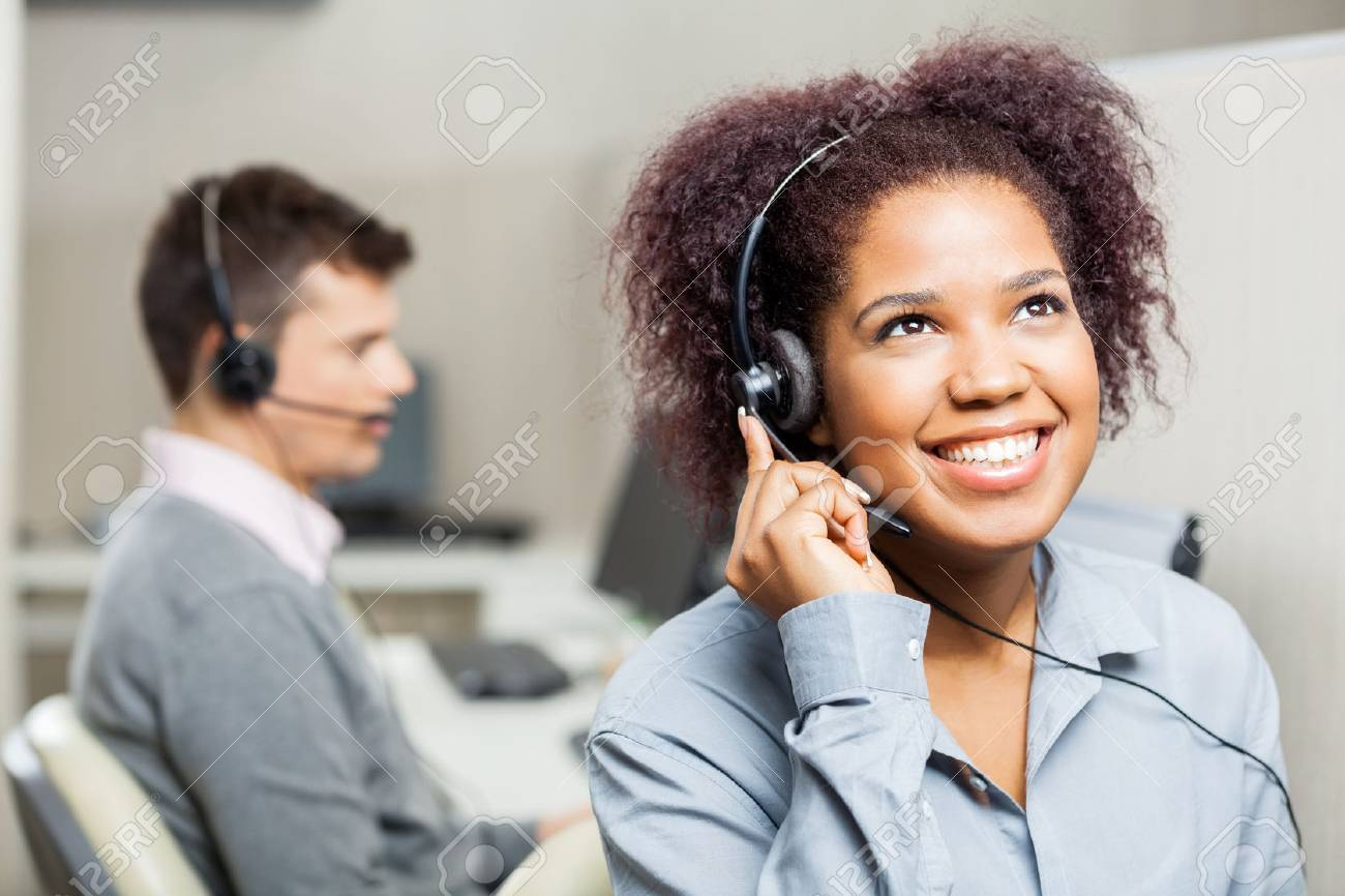 Happy Female Call Center Agent Using Headset In Call Center Archivio Fotografico - 39002256