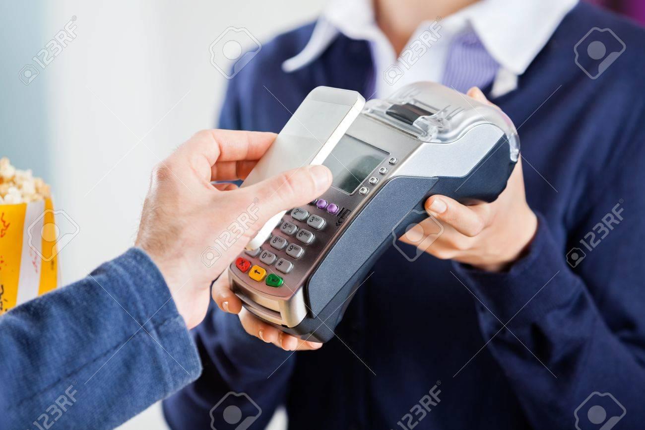 Immagine ritagliata di uomo con la tecnologia NFC per pagare il conto al cinema Archivio Fotografico - 41111623