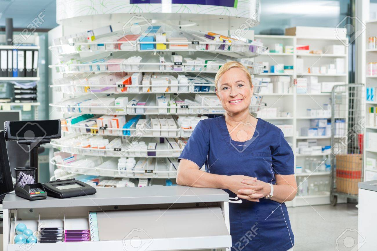 Portrait of confident female pharmacist leaning at cash counter in pharmacy - 43431873