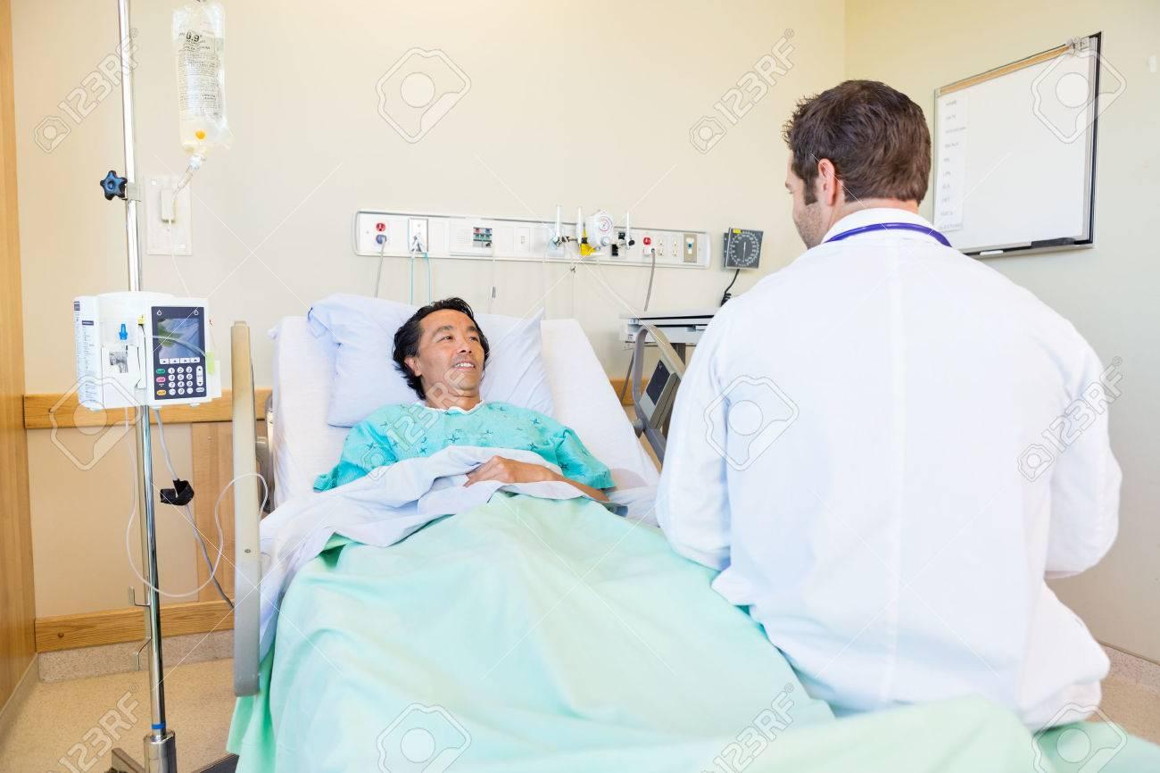 Lachende volwassen patiënt te kijken naar arts terwijl liggend op
