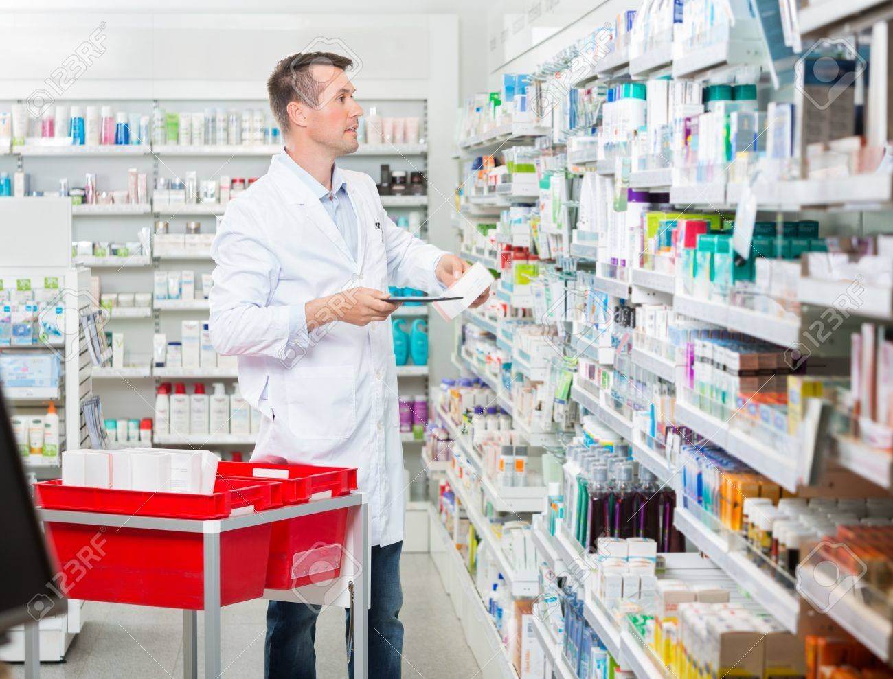 Metà adulto maschio farmacista contando stock, mentre tiene tablet computer in farmacia Archivio Fotografico - 43648451