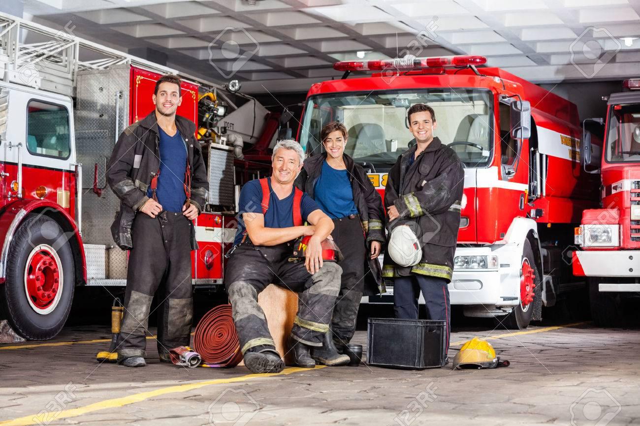 Ritratto di felice team di vigile del fuoco con attrezzature contro i camion alla stazione di fuoco Archivio Fotografico - 43648487