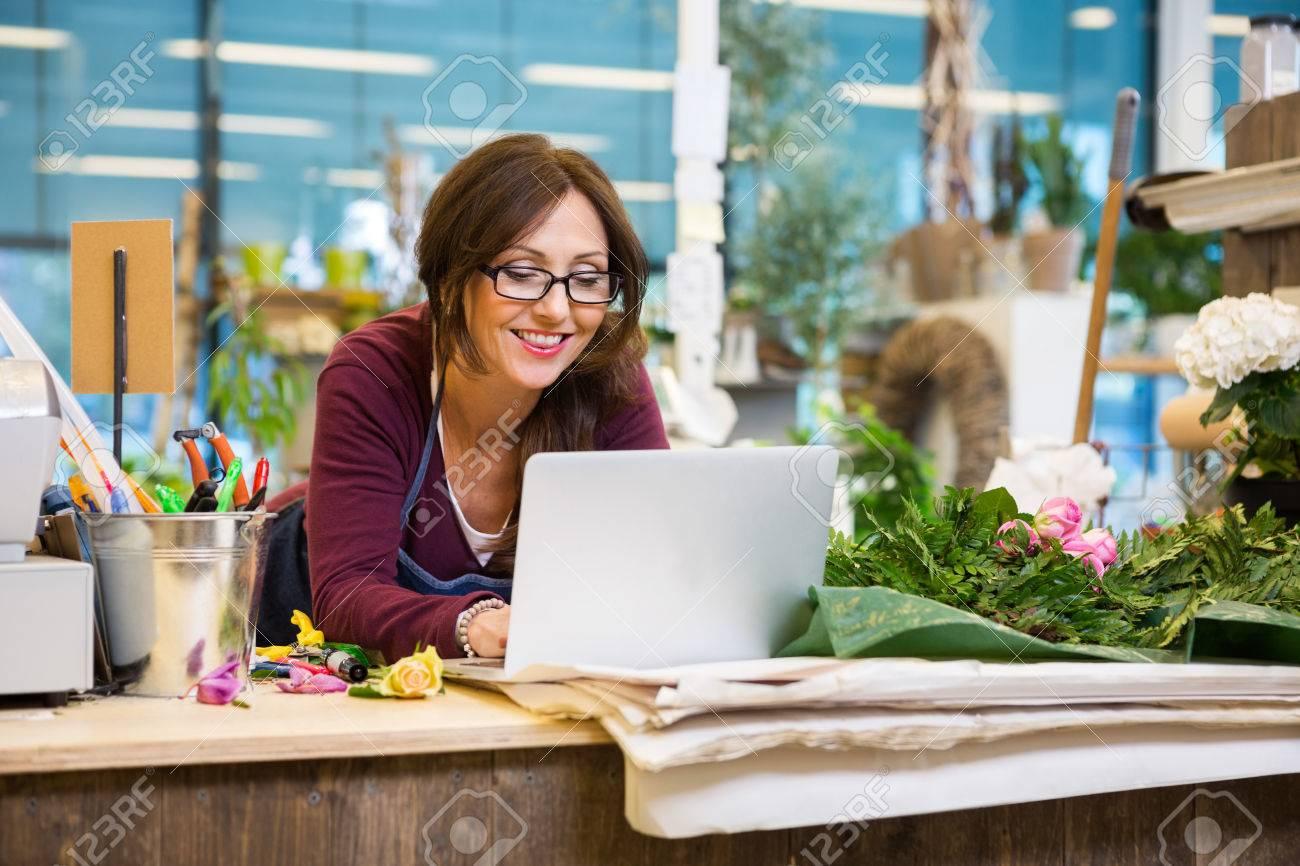 Felice metà degli adulti fiorista femminile utilizzando il computer portatile al contatore nel negozio di fiori Archivio Fotografico - 43648490