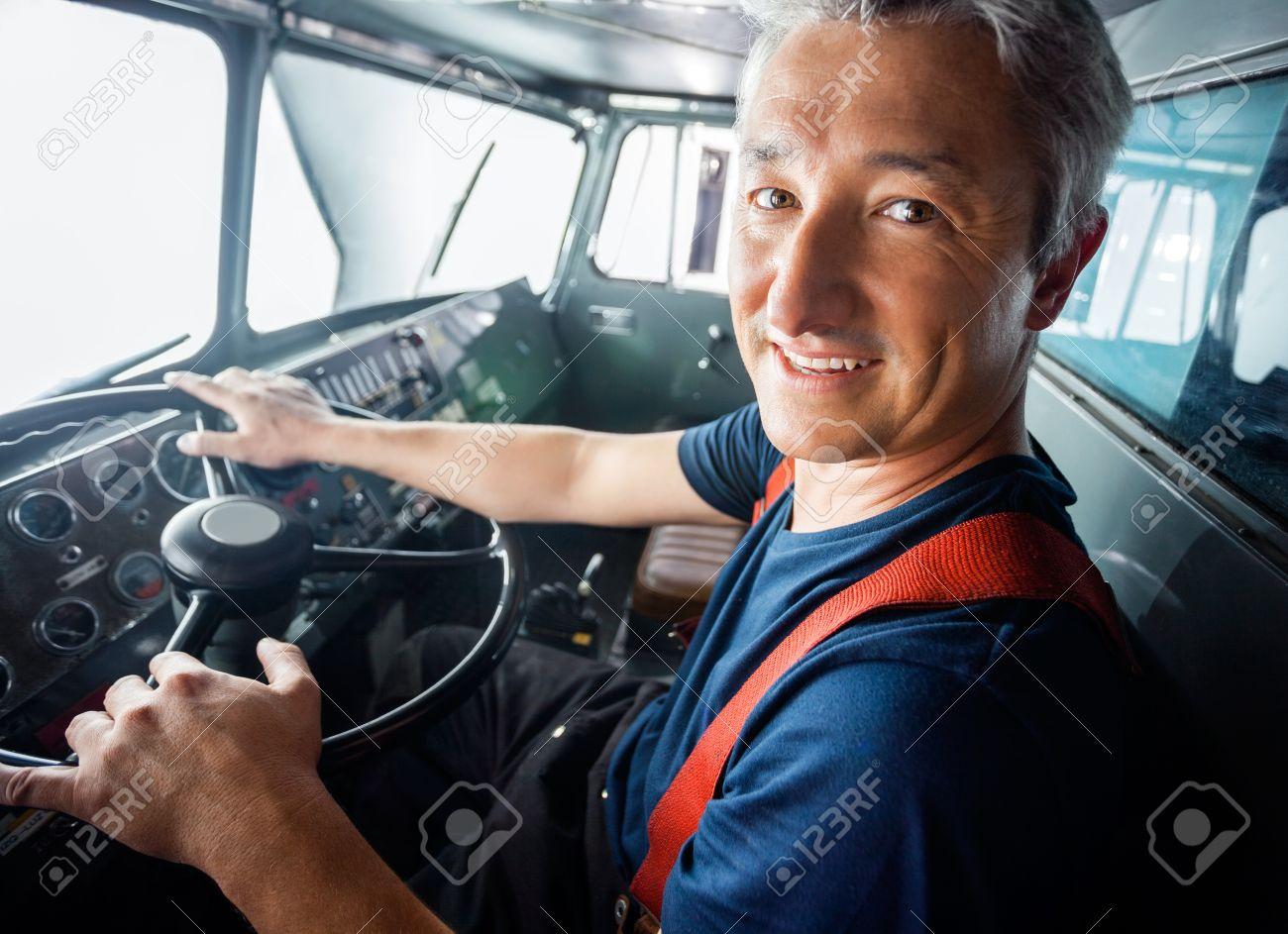 Ritratto di felice pompiere maturo firetruck guida Archivio Fotografico - 43648492
