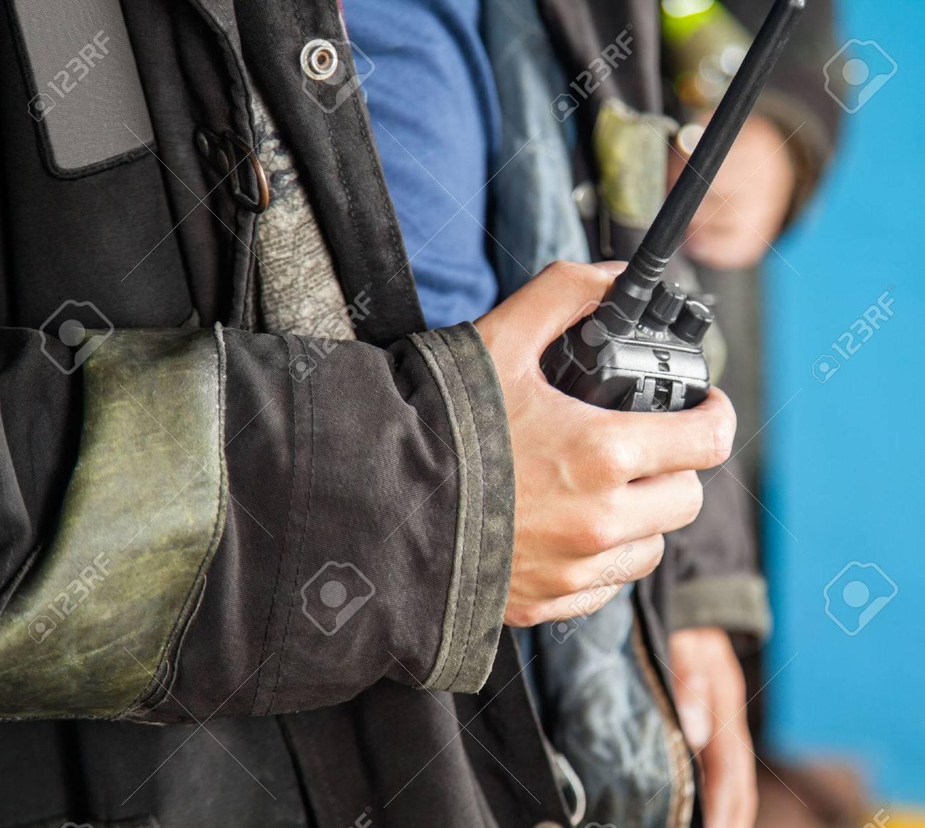 Sezione centrale di vigile del fuoco tenendo walkie-talkie alla stazione di fuoco Archivio Fotografico - 43661096