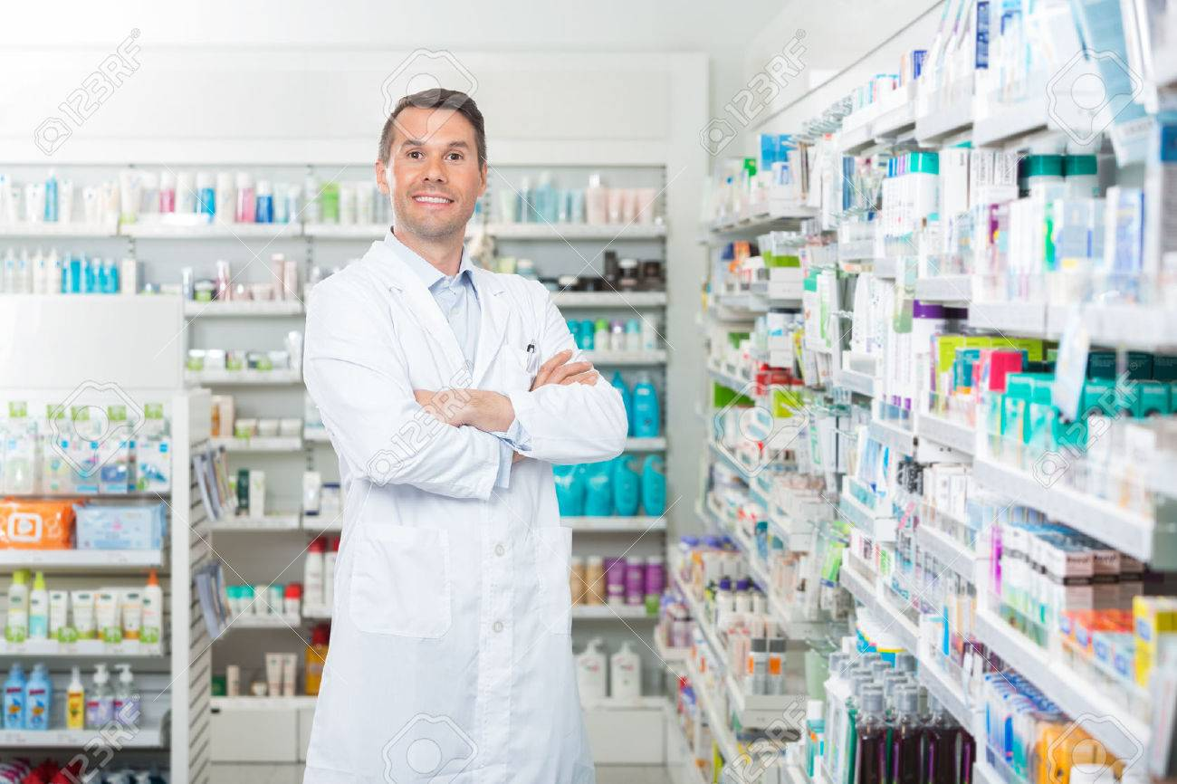 Portrait of smiling mid adult male pharmacist standing arms crossed in pharmacy - 43661132