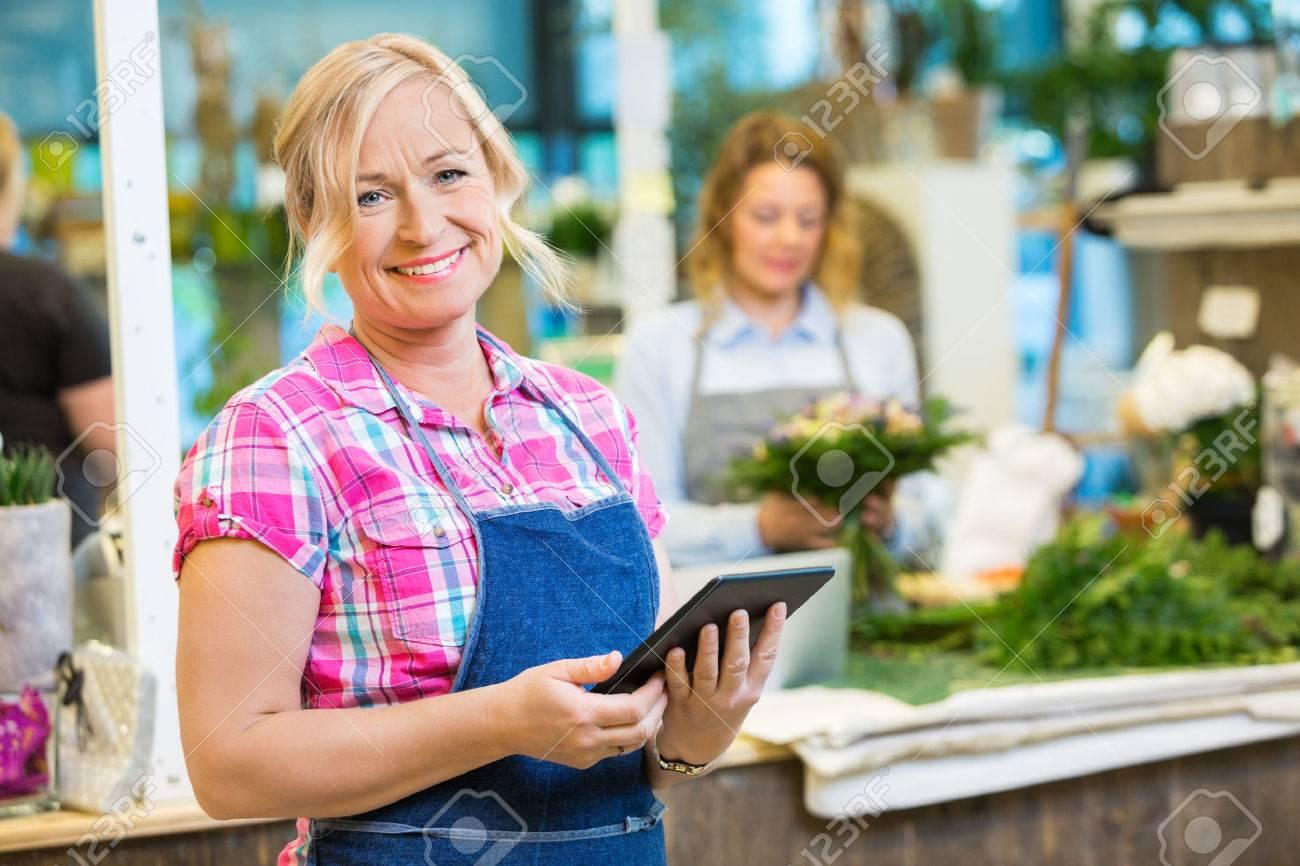 Ritratto di sorridere maturo fiorista femminile in possesso di tavoletta digitale con il collega che lavora in background presso il negozio Archivio Fotografico - 43661170