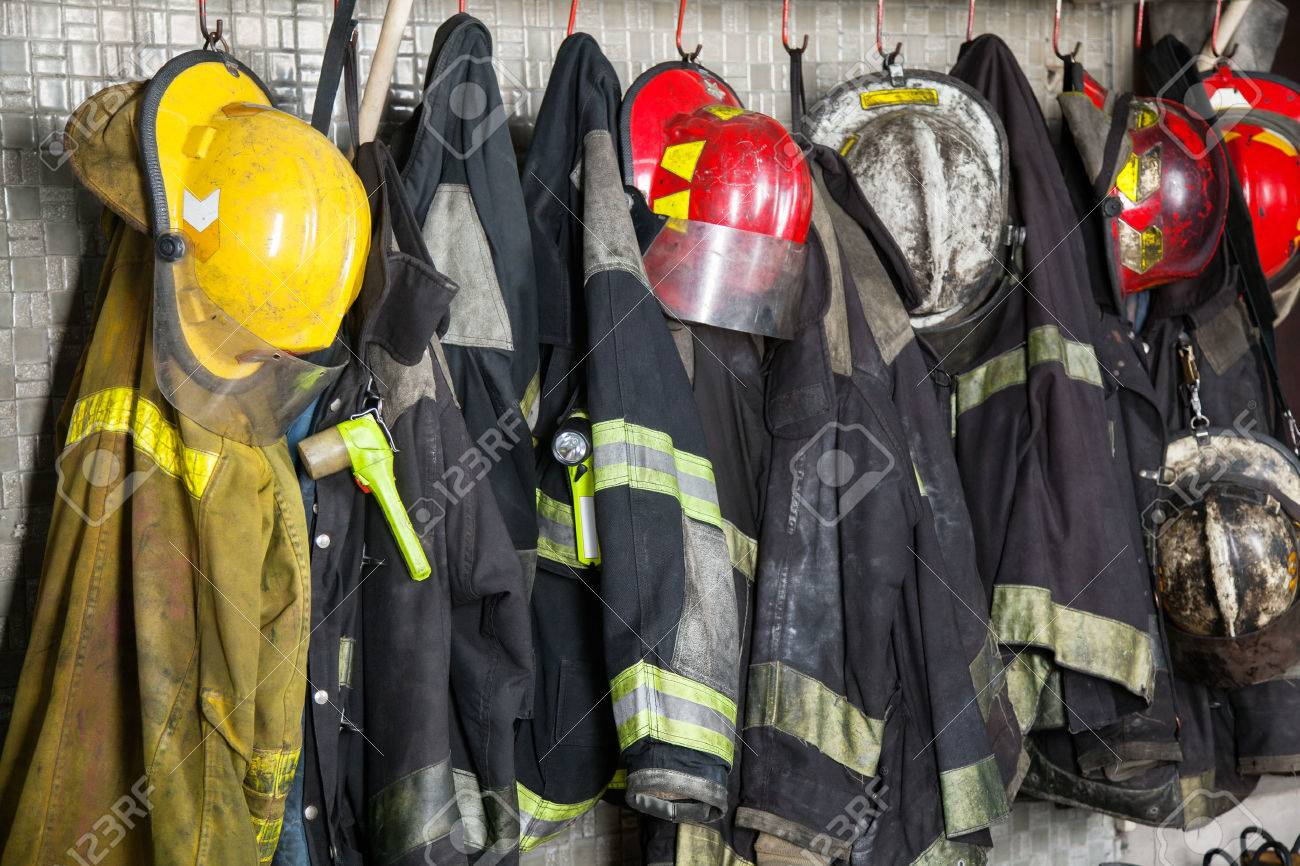 Firefighter suits and helmets hanging at fire station Archivio Fotografico - 44186423