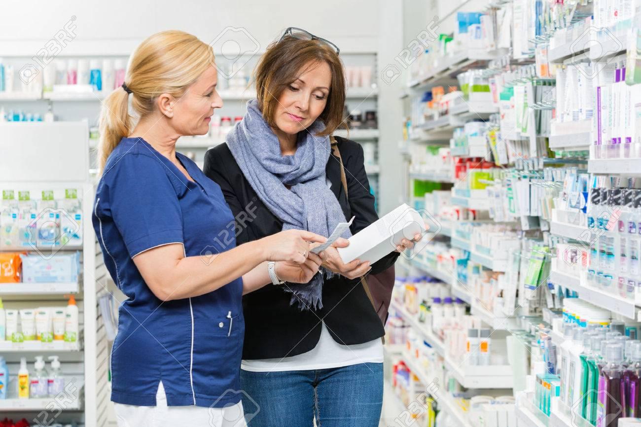 chimico maturo che spiega i dettagli del prodotto al cliente femminile in farmacia Archivio Fotografico - 44324053