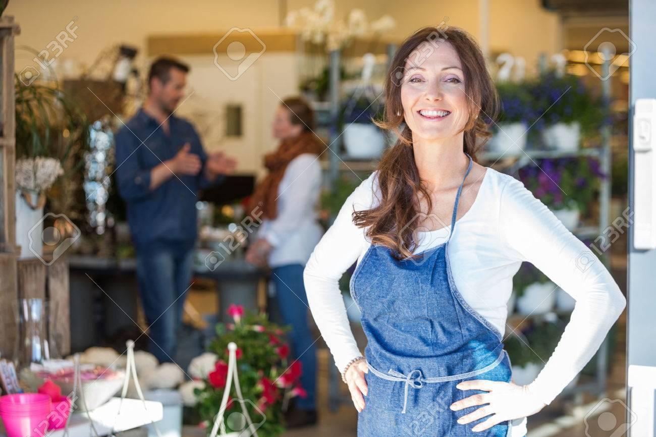 Ritratto di donna sorridente con i clienti in background al negozio di fiori Archivio Fotografico - 44324035