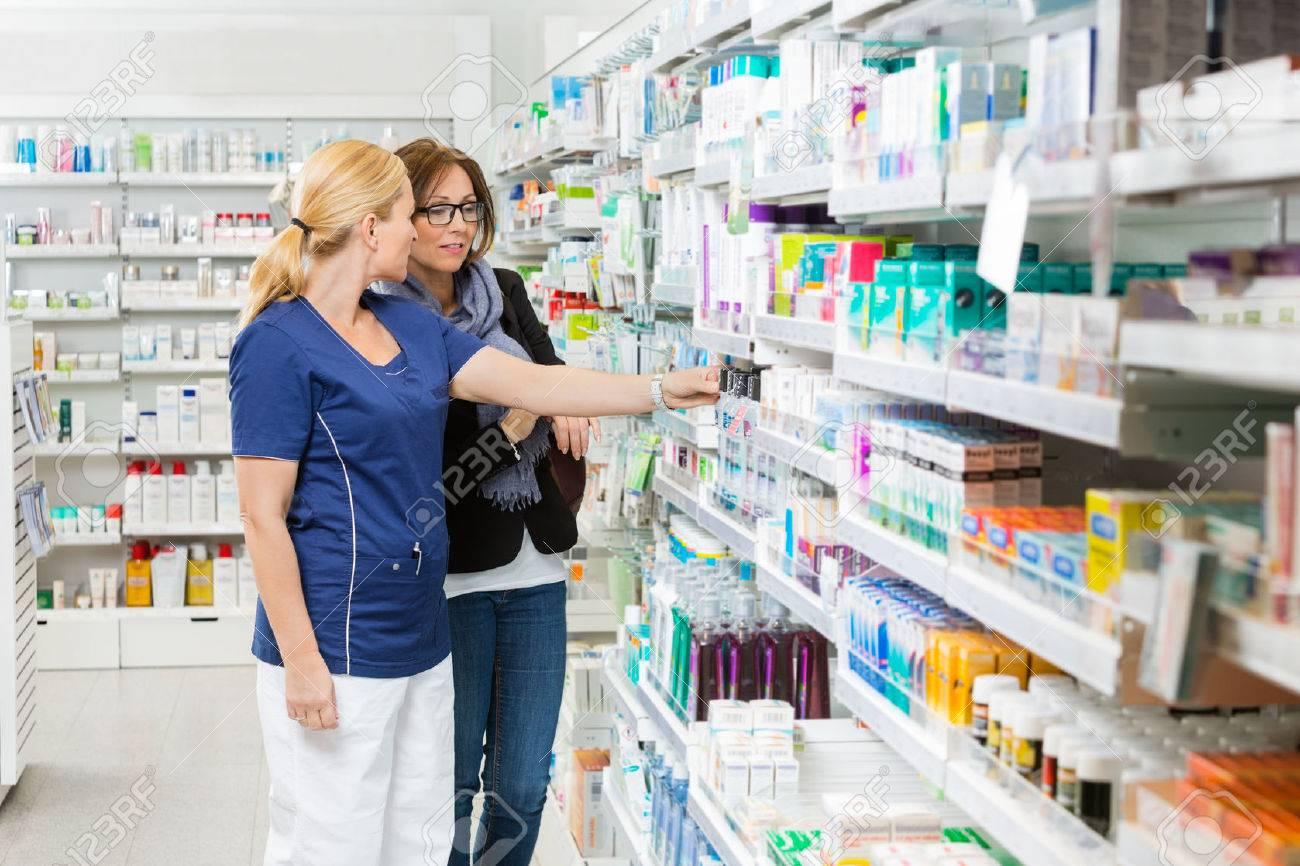 Farmacista femminile rimozione del prodotto per il cliente dalla mensola in farmacia Archivio Fotografico - 46403609