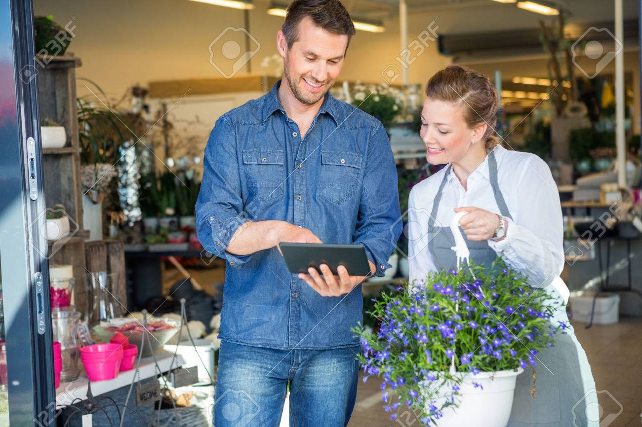 Male customer using digital tablet while standing by florist holding potted plant in shop Standard-Bild - 46404348