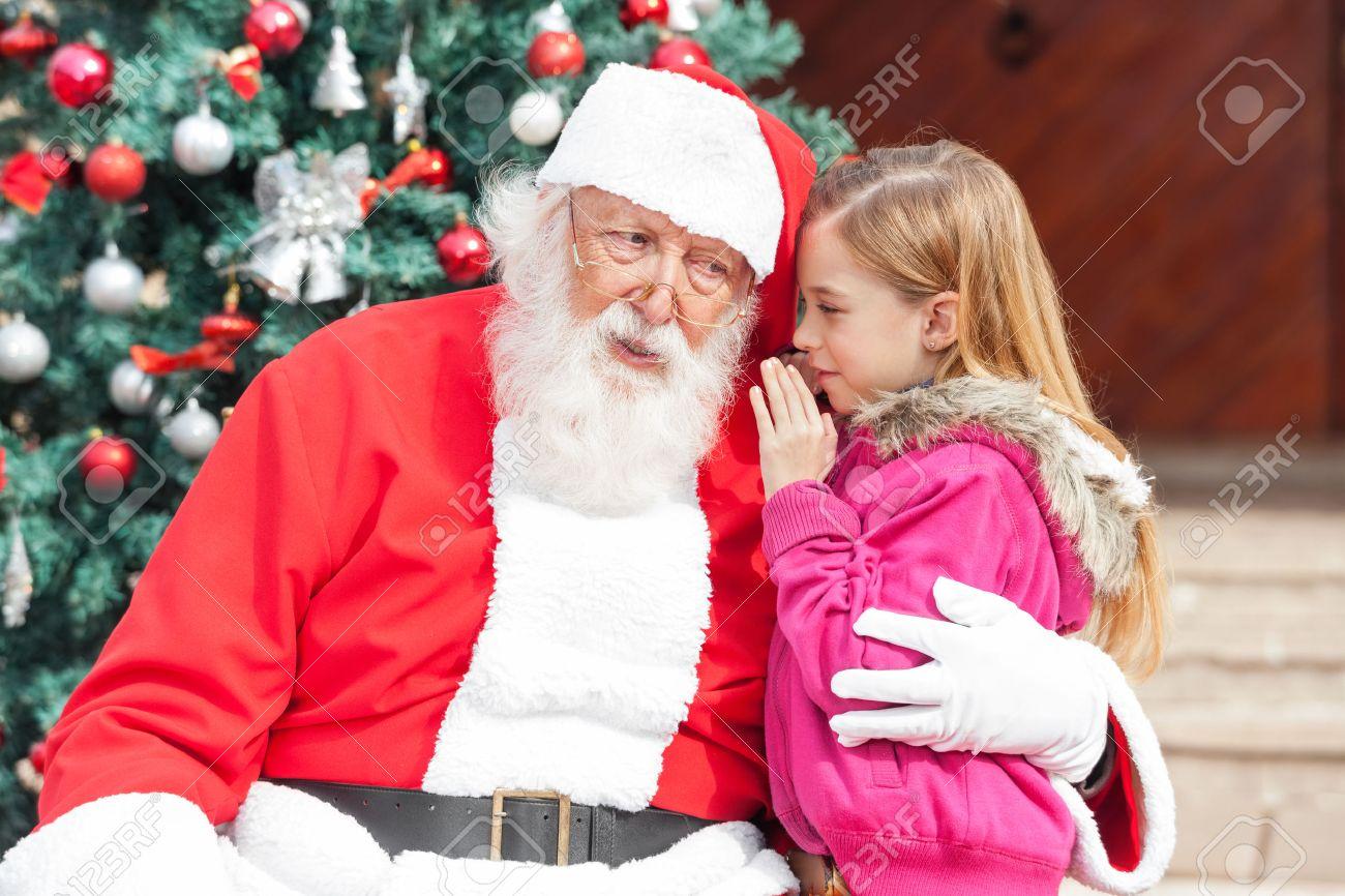 Girl telling wish in Santa Claus's ear against Christmas tree Standard-Bild - 46404614