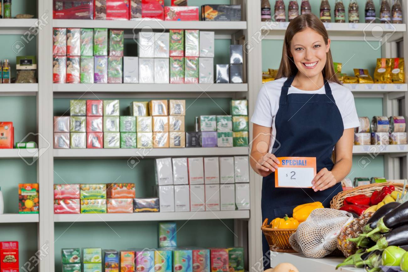 Portrait Of Confident Saleswoman Displaying Pricetag In Grocery ...