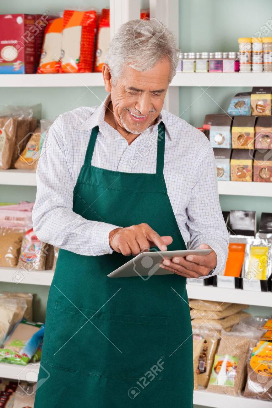 Happy senior male owner using digital tablet in supermarket Archivio Fotografico - 46404912