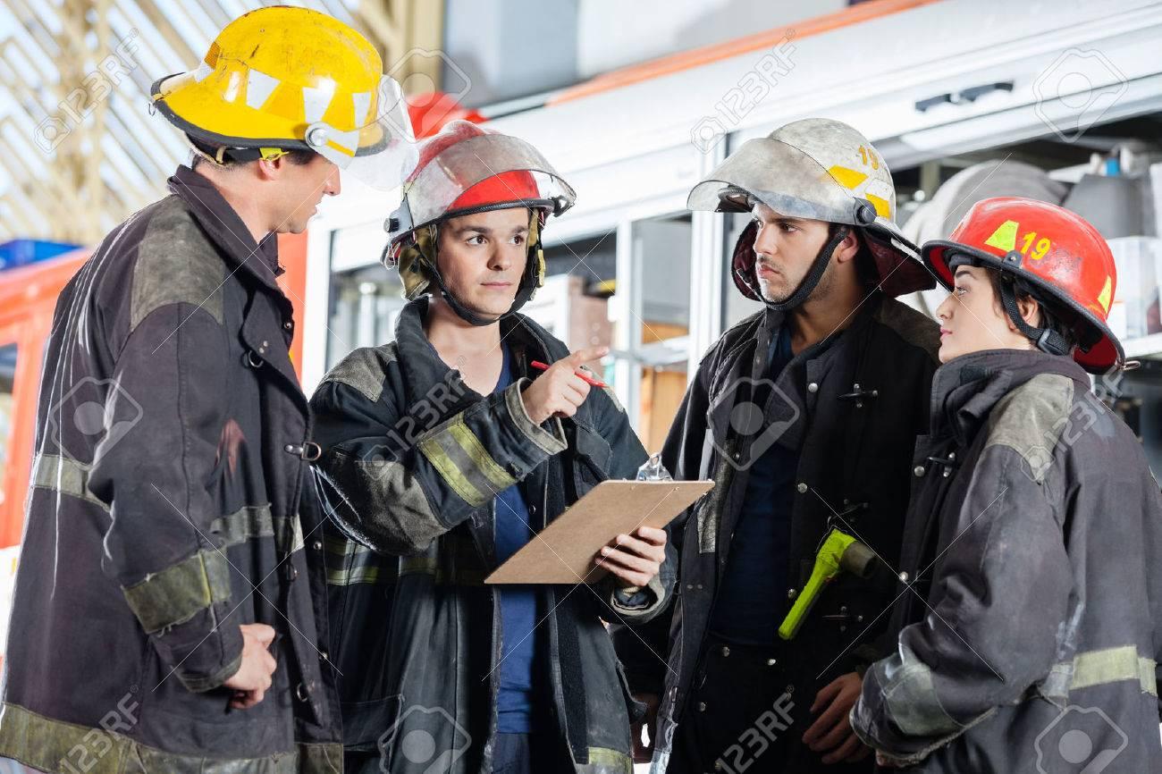 pompiere maschio gesticolando mentre discute con i colleghi alla stazione dei pompieri Archivio Fotografico - 46595039