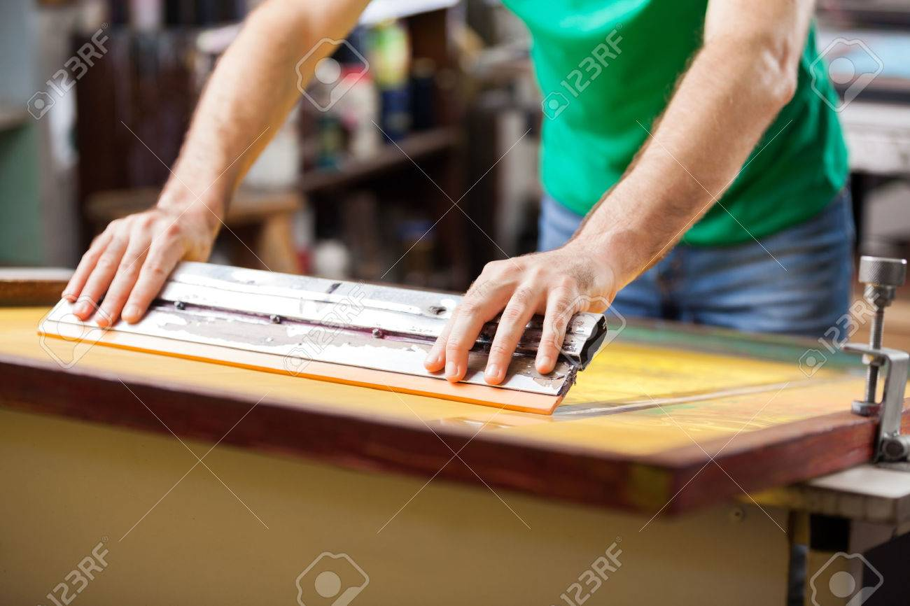 Midsection mid adult worker using squeegee in factory Standard-Bild - 46944760