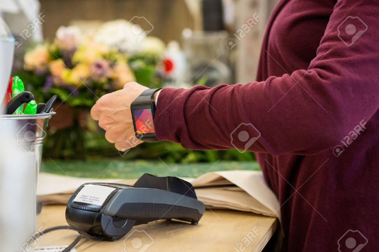 Cropped image of female customer paying through smart watch at flower shop Standard-Bild - 46945592