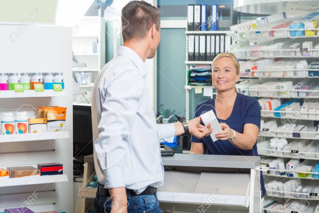 Smiling female chemist giving product to male customer in pharmacy Standard-Bild - 46945641