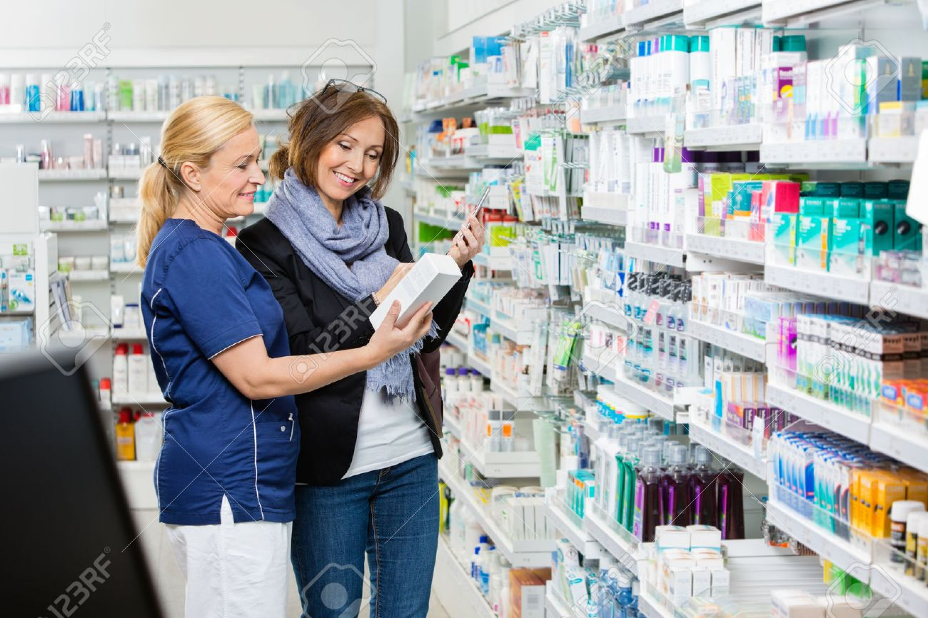 Sorridente assistente femminile mostrando prodotto al cliente azienda di telefonia cellulare in farmacia Archivio Fotografico - 46945756