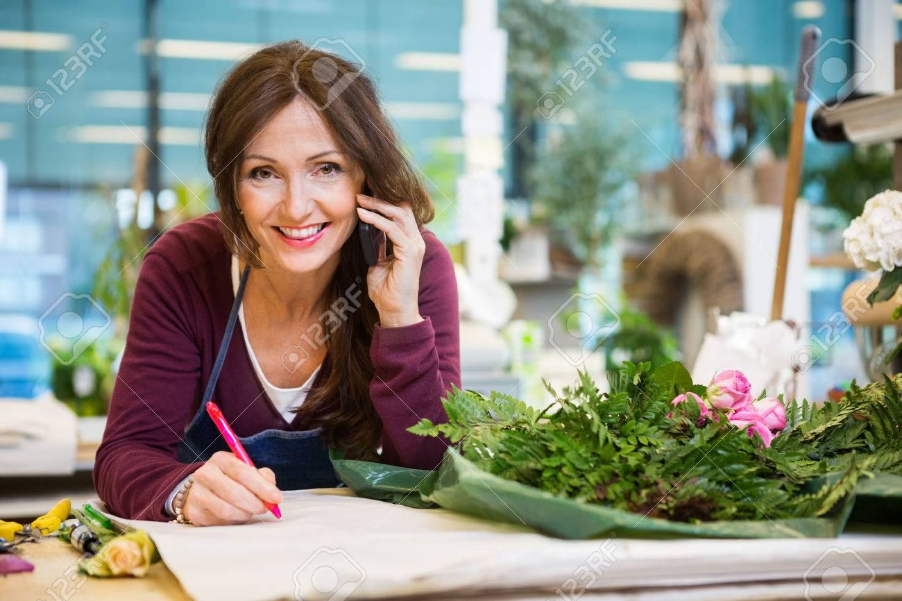 Portrait of happy female florist using mobile phone while writing on paper in flower shop Standard-Bild - 46945758