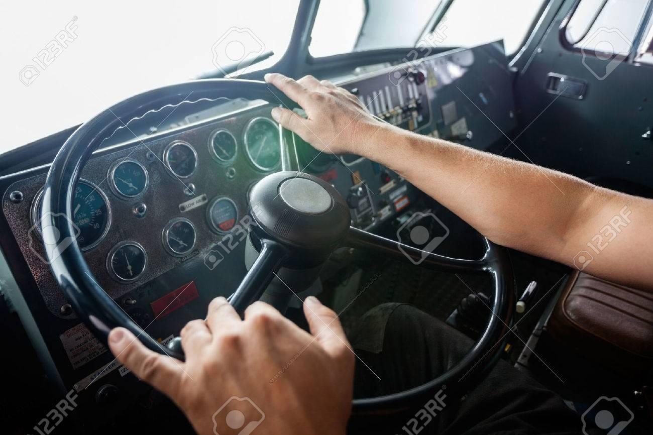 Cropped image of fireman's hands holding steering wheel of firetruck at station Standard-Bild - 47226109