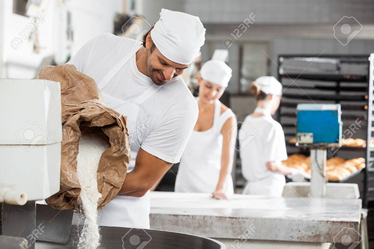 Smiling male baker pouring flour in kneading machine at bakery Standard-Bild - 47226135