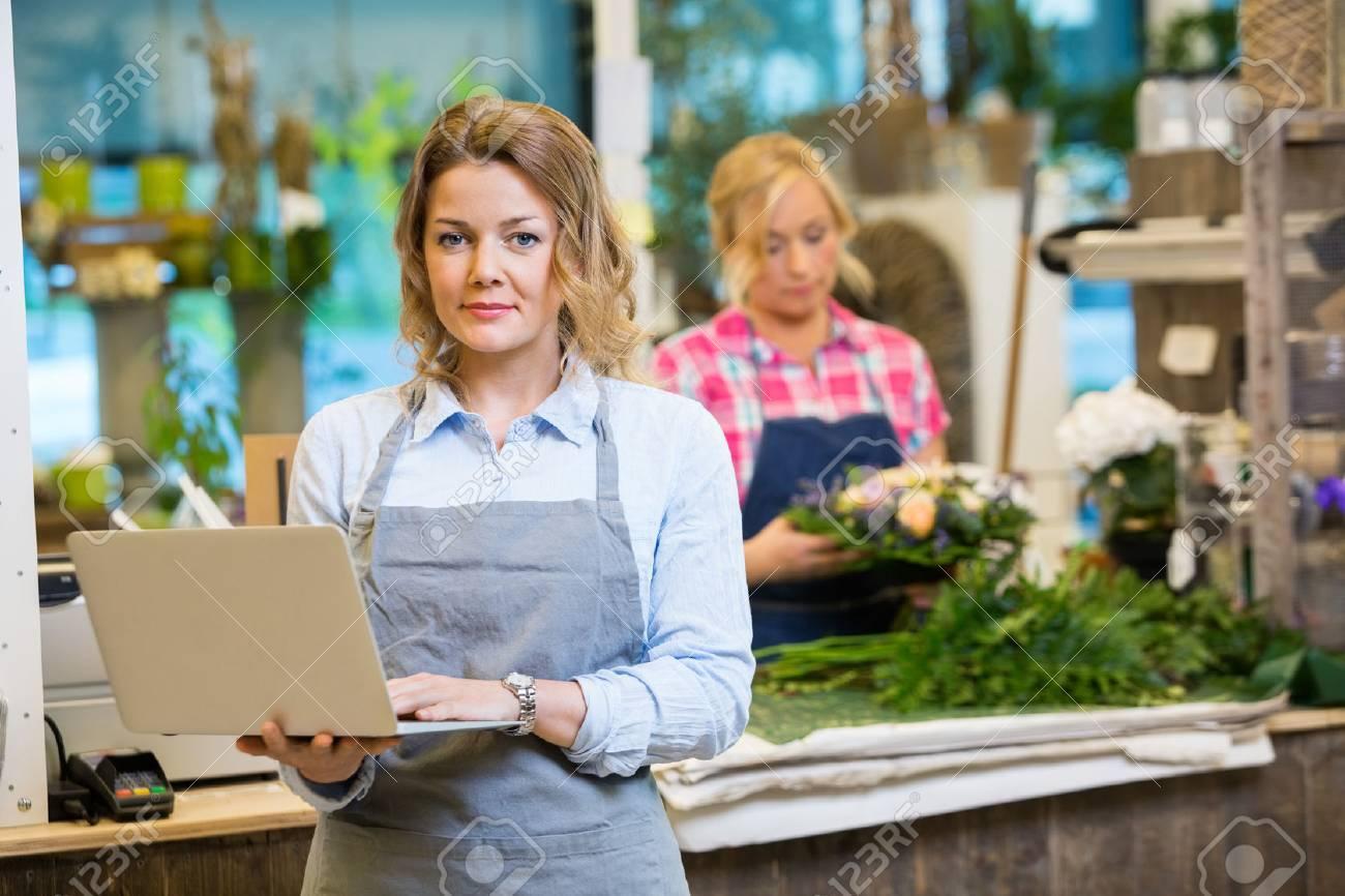 Ritratto di fiorista femminile utilizzando il computer portatile con il collega che lavora in fondo al negozio di fiori Archivio Fotografico - 47407121