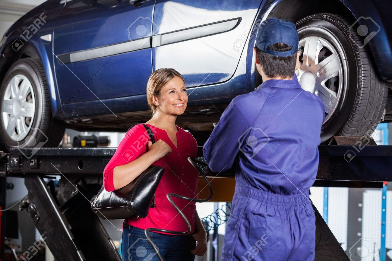 Felice cliente femminile guardando meccanico ricarica pneumatico auto a garage Archivio Fotografico - 47938166