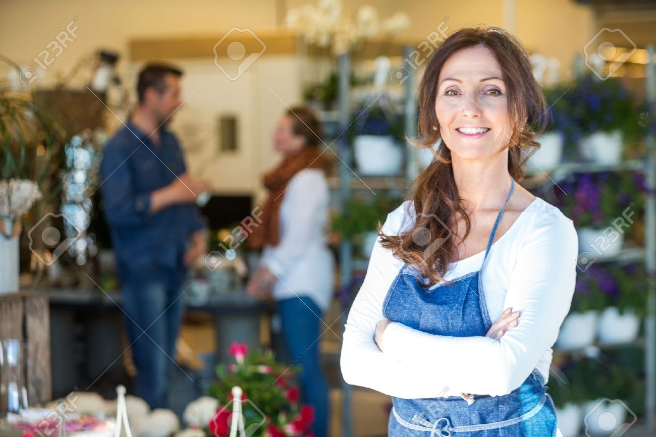 Portrait of smiling mid adult florist with customers in background at flower shop Standard-Bild - 47938293