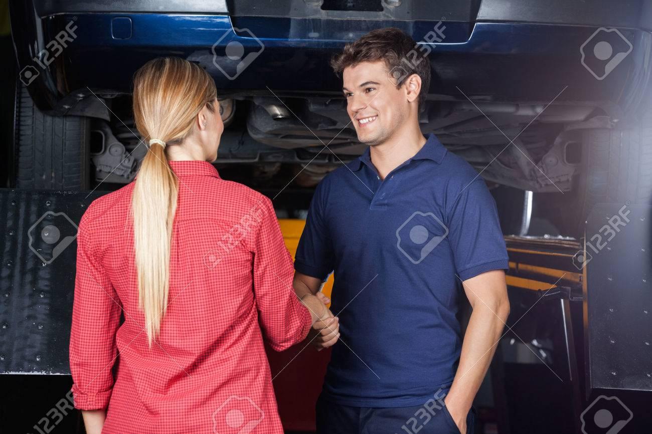 Smiling male mechanic shaking hand with customer at auto repair shop Standard-Bild - 53299040