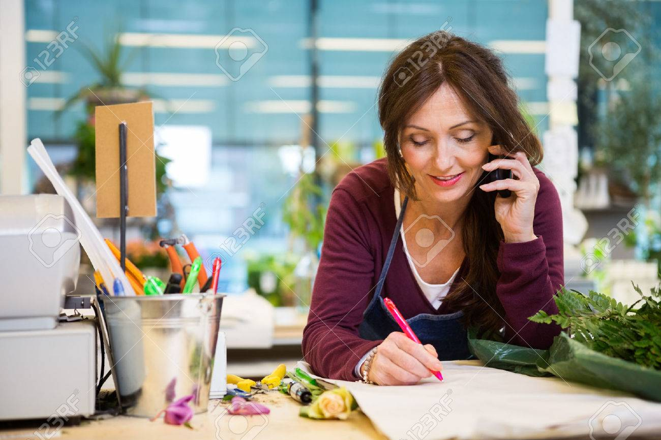 Female florist using mobile phone while writing on paper in flower shop - 53300982
