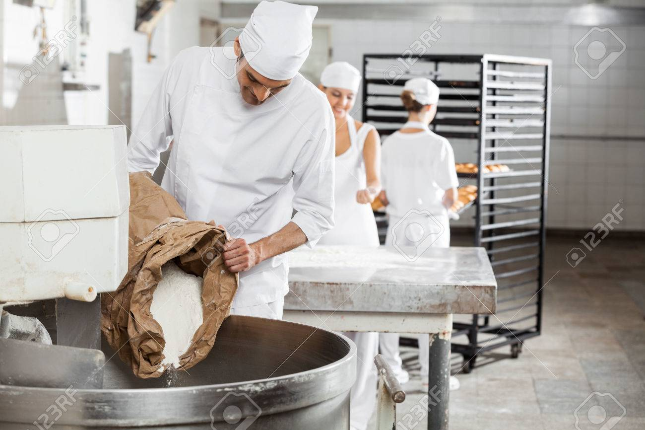 Mature male baker pouring flour in kneading machine at bakery - 53770593