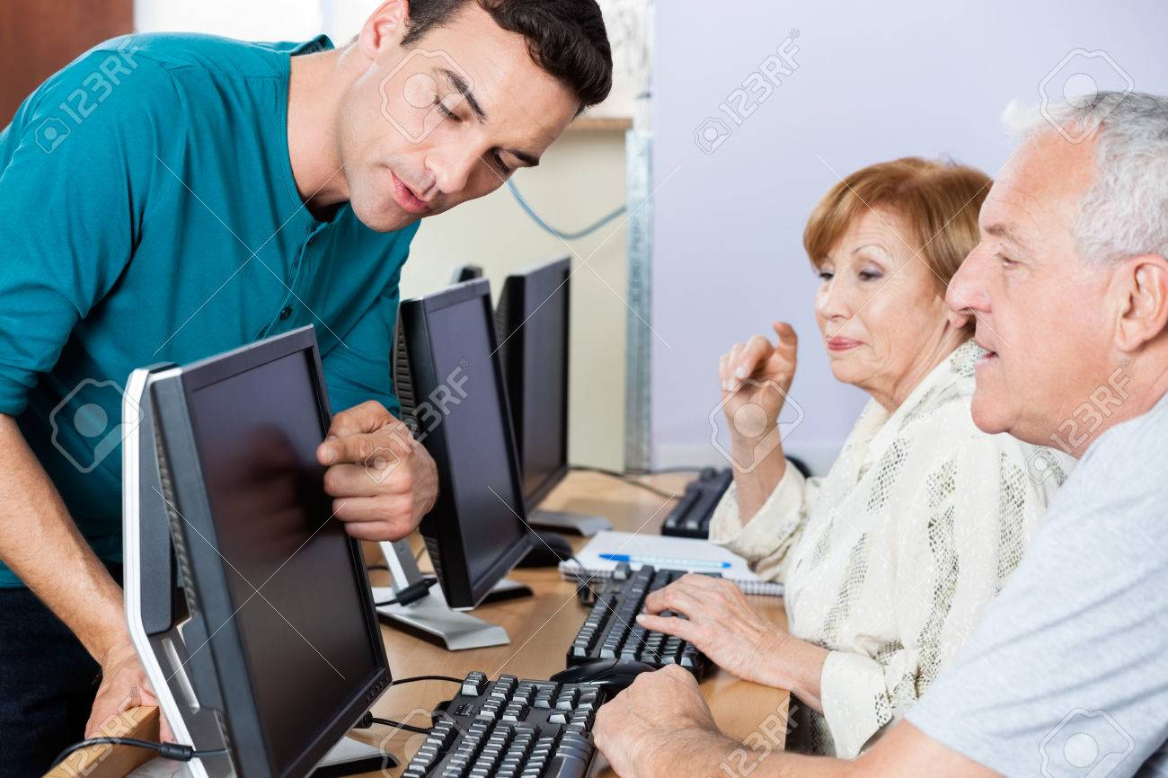 Young male tutor guiding senior students in using computer at classroom Standard-Bild - 53772436