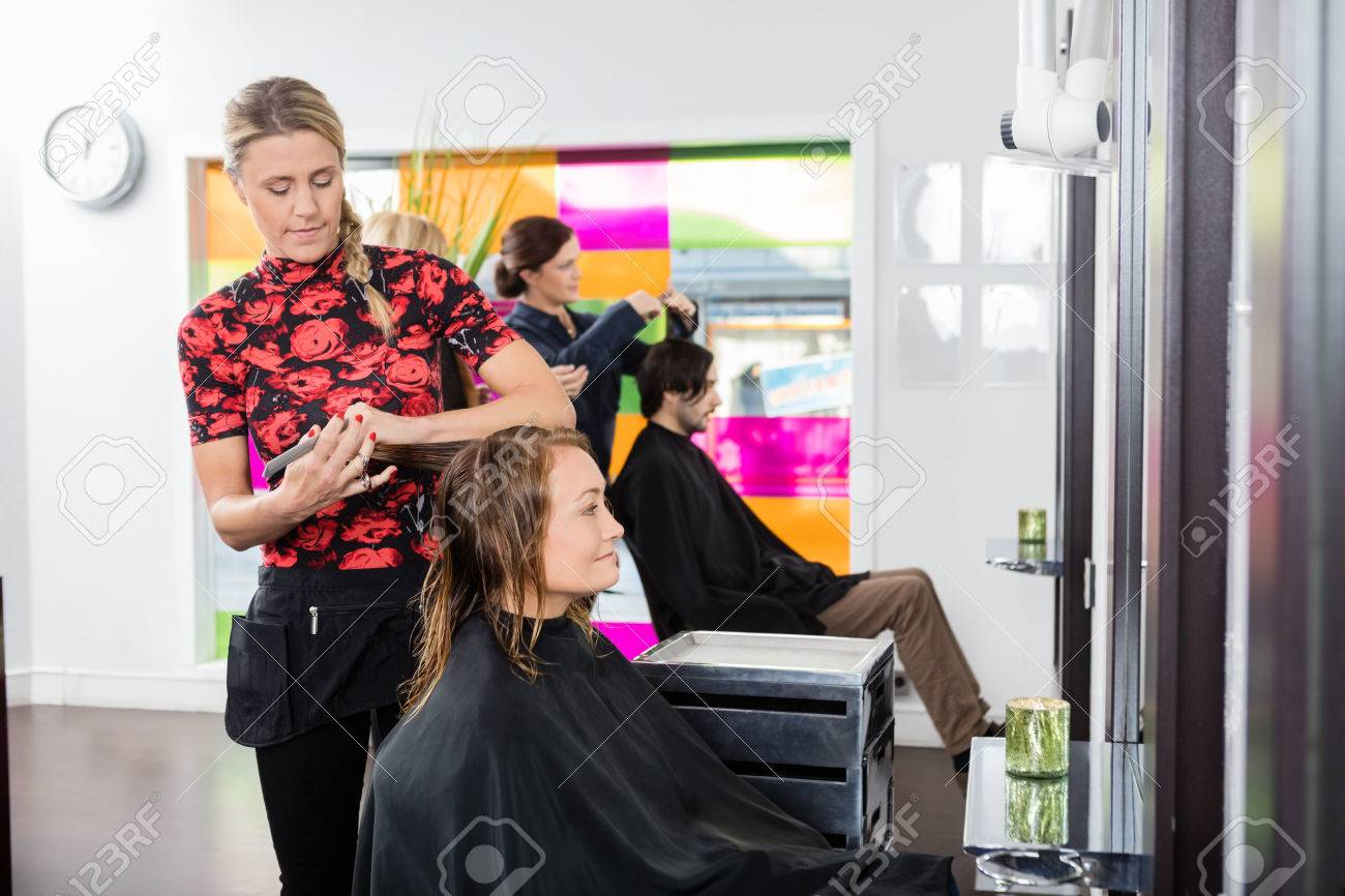 Mid Adult Woman Getting New Haircut By Female Hairstylist At Stock