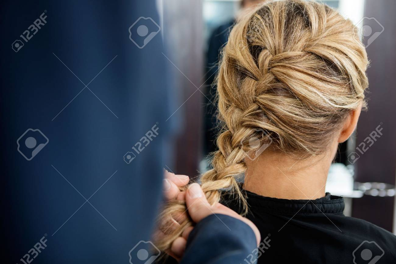 Cropped image of hairdresser braiding client's hair in salon Standard-Bild - 55568697