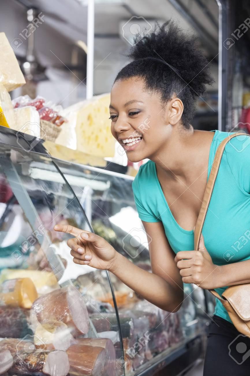4261a976d7 Cliente femminile felice che esamina i prodotti in vetrina in drogheria