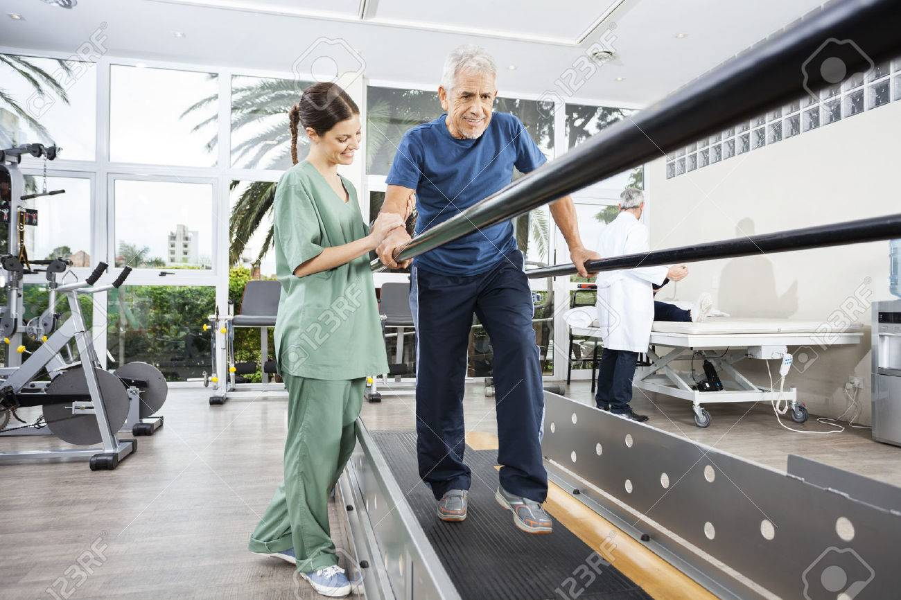 Female physiotherapist standing by smiling senior patient walking between parallel bars in rehab center - 56878866