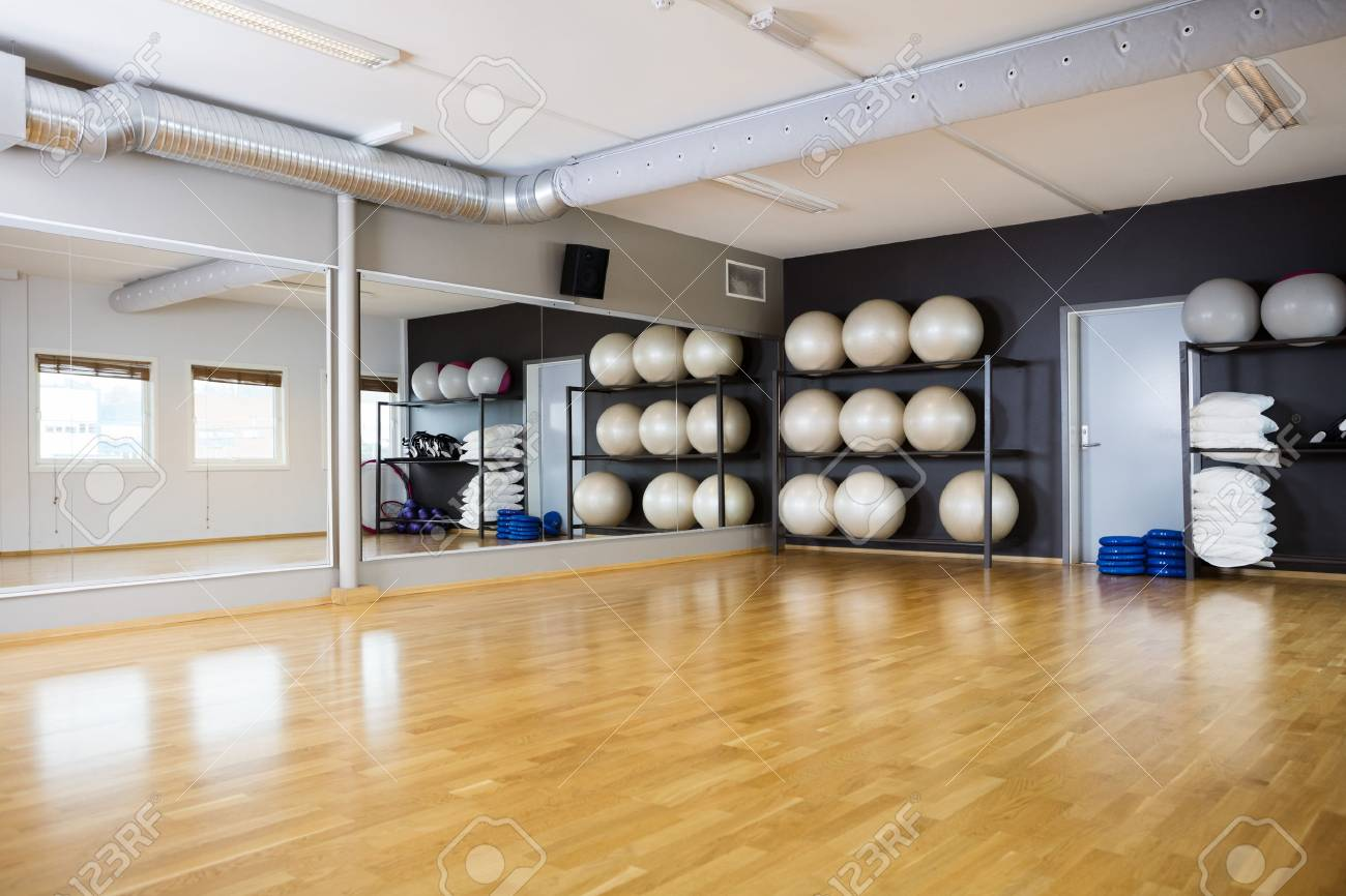 Yoga balls arranged in shelves by mirror at gym - 56878871
