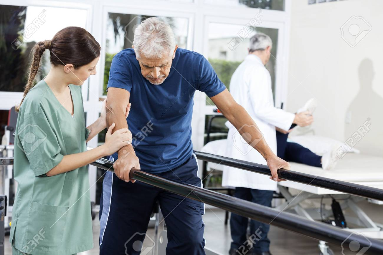 Female physiotherapist standing by senior patient walking between parallel bars in rehabilitation center - 56878899